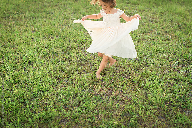 Girl Twirling In A Grassy Area by Alison Winterroth for Stocksy United