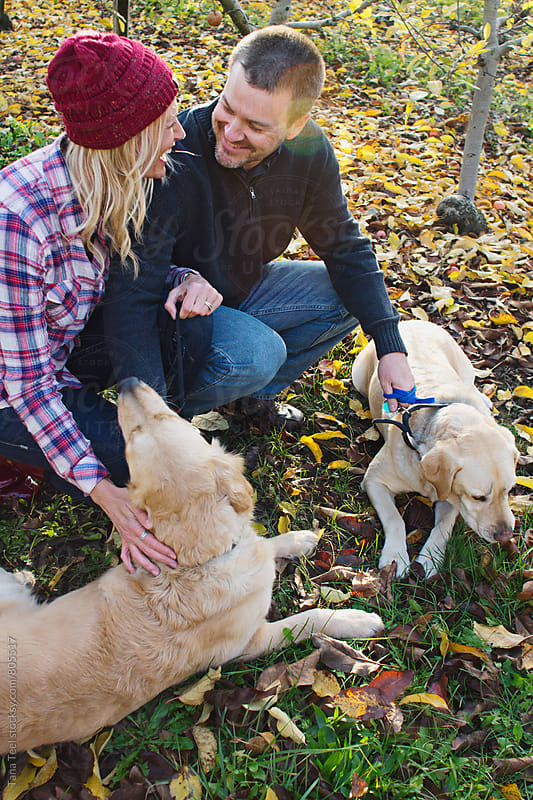 Couple kneels down to pet their dogs by Tana Teel for Stocksy United