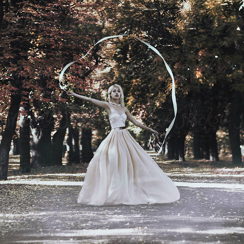 Beautiful girl playing with silk tape outdoors by Jovana Rikalo for Stocksy United