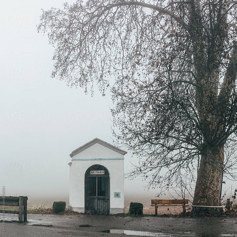 Very tiny chapel entitled to Holy Mary in open countryside in Italy, foggy morning by Laura Stolfi for Stocksy United
