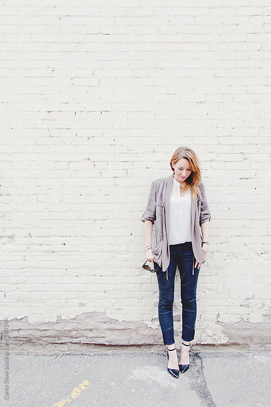 Stylish young woman standing against white brick wall by Carey Shaw for Stocksy United