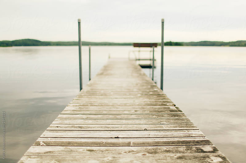 pier over a lake on a cloudy day by Kelly Knox for Stocksy United
