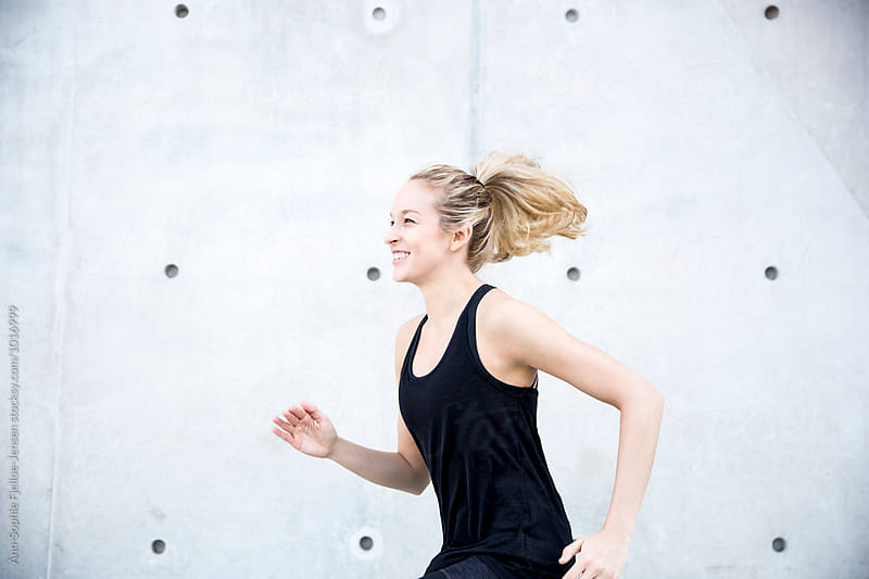 Woman sprinting outdoors by Ann-Sophie Fjelloe-Jensen for Stocksy United