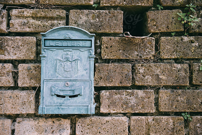 Blue mailbox on a wall by Adrian Cotiga for Stocksy United