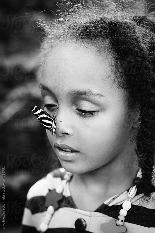 Portrait of young girl with a striped butterfly sitting on her nose by anya brewley schultheiss for Stocksy United