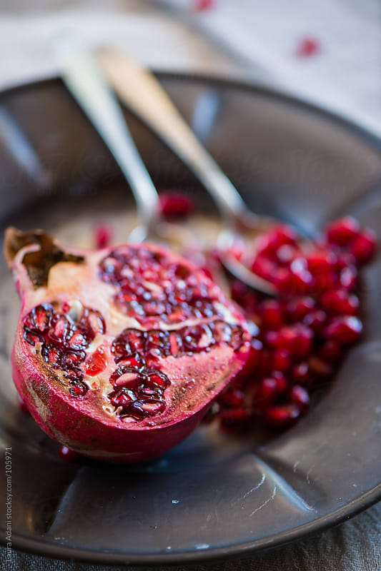 a pomegranate cut into half by Laura Adani for Stocksy United