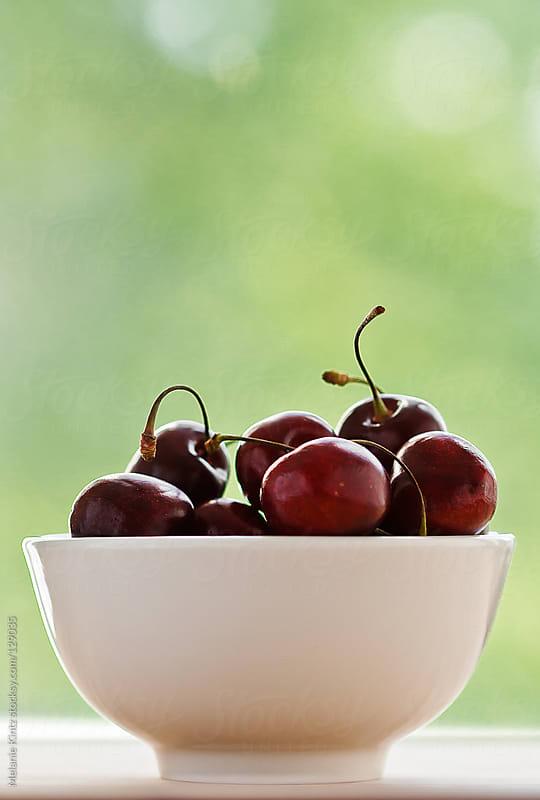 Cherries in white bowl  by Melanie Kintz for Stocksy United