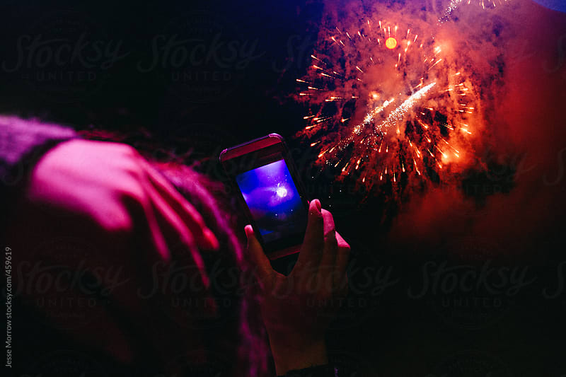 Woman holds phone in her hand while taking picture of fireworks by Jesse Morrow for Stocksy United