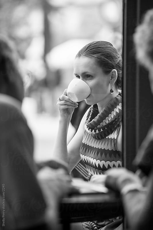 Woman sipping her coffee with friends at a street cafe by Shelly Perry for Stocksy United