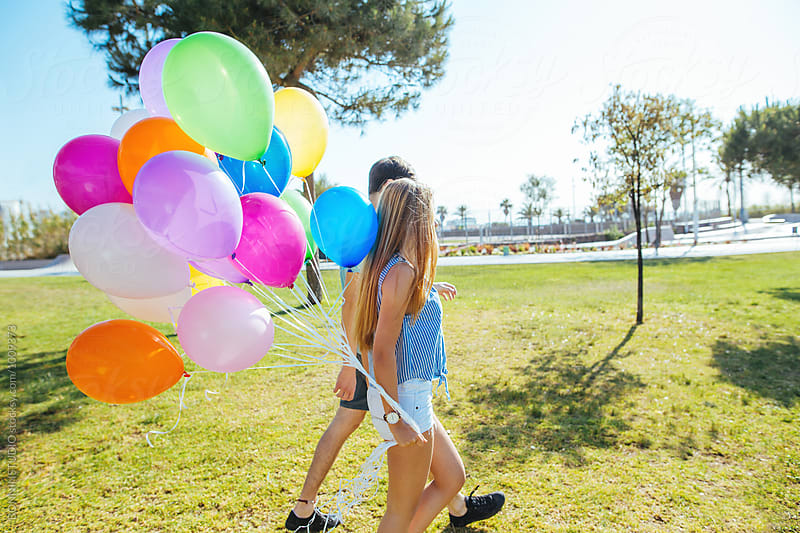 Teenage couple holding colorful balloons in a park on a sunny day. by BONNINSTUDIO for Stocksy United