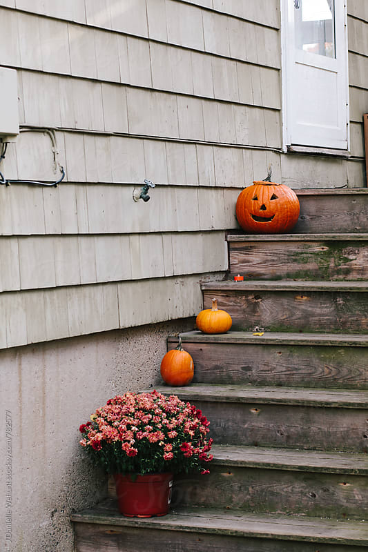 Pumpkins sitting on wooden stairs outside. by J Danielle Wehunt for Stocksy United