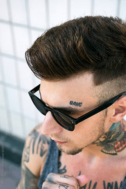 Tattooed young man in sunglasses by T-REX & Flower for Stocksy United