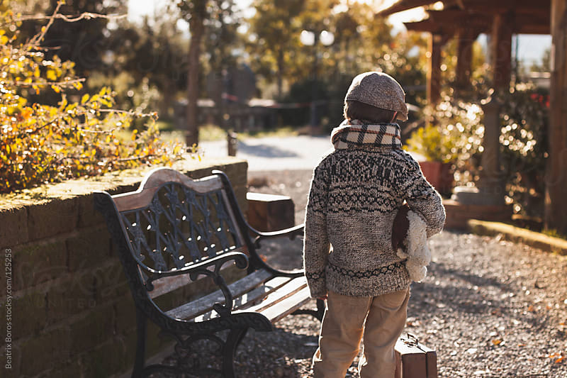 Little traveller boy waiting in a park with his suitcase by Beatrix Boros for Stocksy United