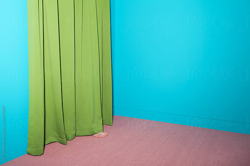 person hiding behind a green curtain in an emtpy room by Ulaş and Merve for Stocksy United