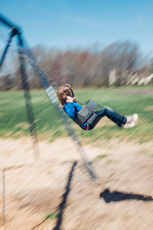Child swinging in the spring with motion blur  by Cameron Whitman for Stocksy United