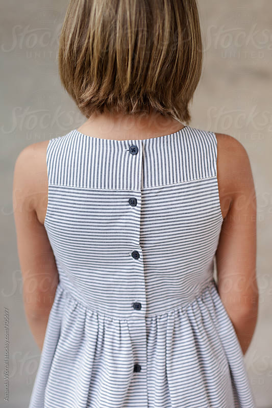 Girl wearing a striped dress with button details on the back by Amanda Worrall for Stocksy United