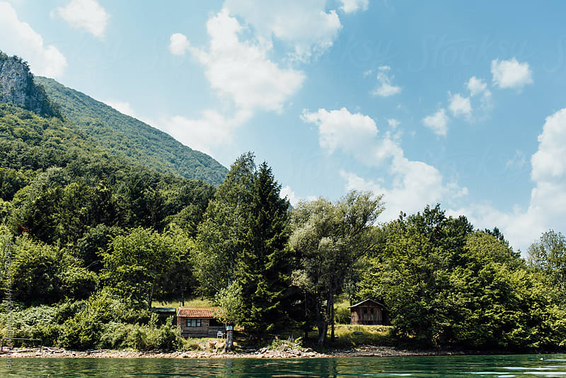 Beautiful cottage house on the lake, placed under the mountain by Boris Jovanovic for Stocksy United
