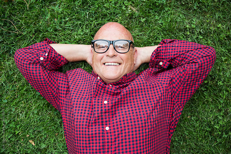 Portrait of senior man smiling at camera while lying on grass by Inuk Studio for Stocksy United