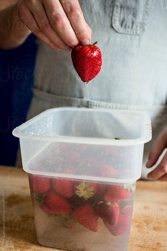 Man making Strawberry Puree by Jenny Sathngam for Stocksy United