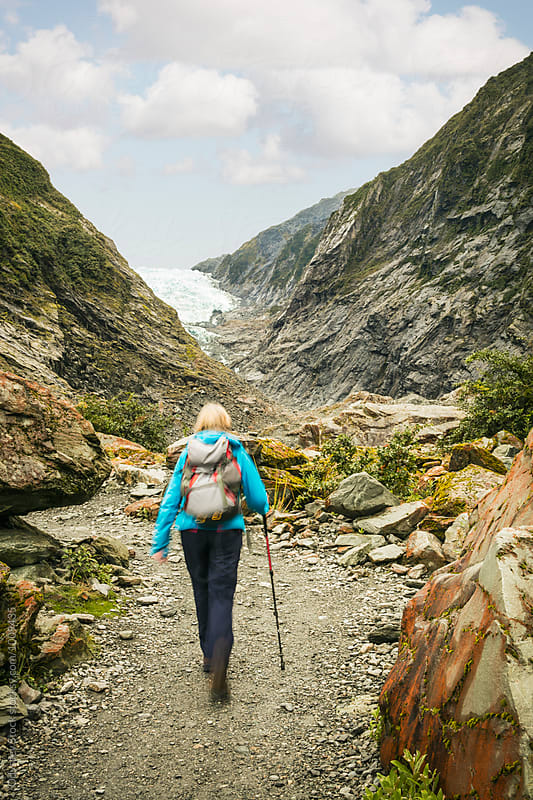 Woman Hiking on Trail Towards Mountain Glacier by Odyssey Stock for Stocksy United