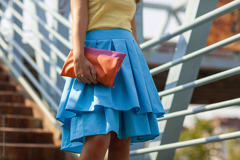 Woman in a blue skirt standing on a stairway.  by Mosuno for Stocksy United
