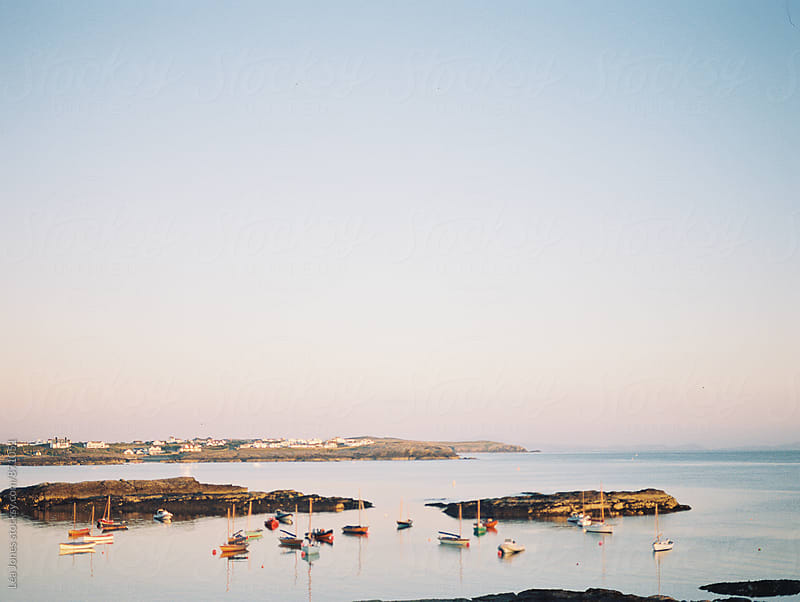 little sailing boats on a quiet sea at sunset by Léa Jones for Stocksy United