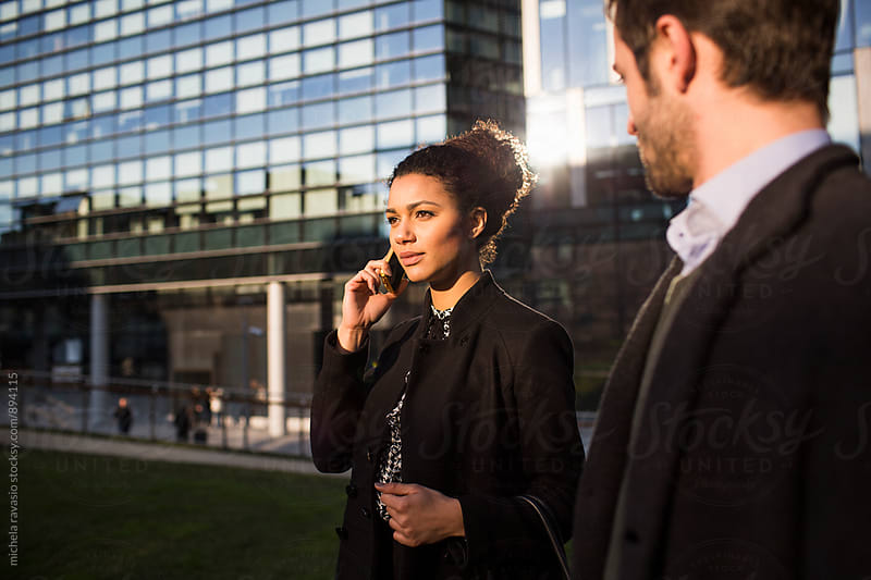 Attractive business woman at cellphone outdoors by michela ravasio for Stocksy United