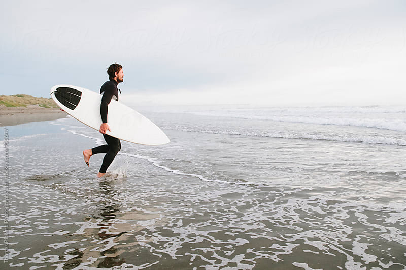 Surfer running into the ocean with surfboard, New Zealand by Thomas Pickard for Stocksy United