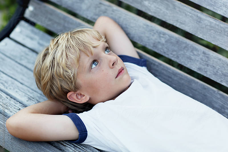 boy lying on a park bench by Kelly Knox for Stocksy United