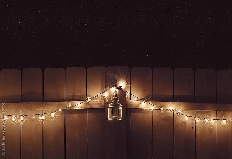 Christmas lights draped on a fence at night with lantern by Rachel Bellinsky for Stocksy United