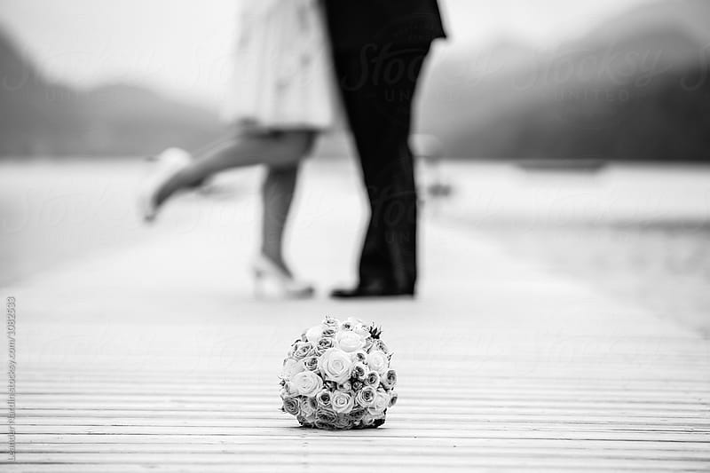 detail of a bridal bouquet in front of bridal couple on a jetty - black and white by Leander Nardin for Stocksy United