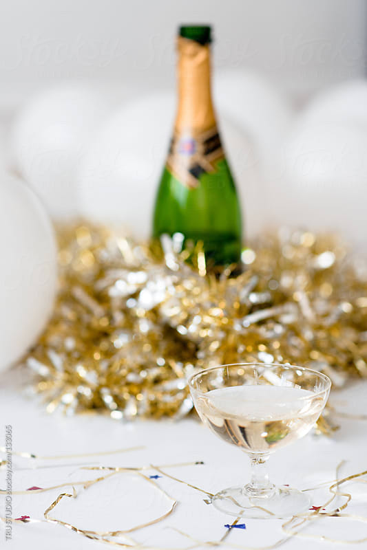Champagne glass in front of bottle at a party with balloons and confetti and gold streamers by TRU STUDIO for Stocksy United