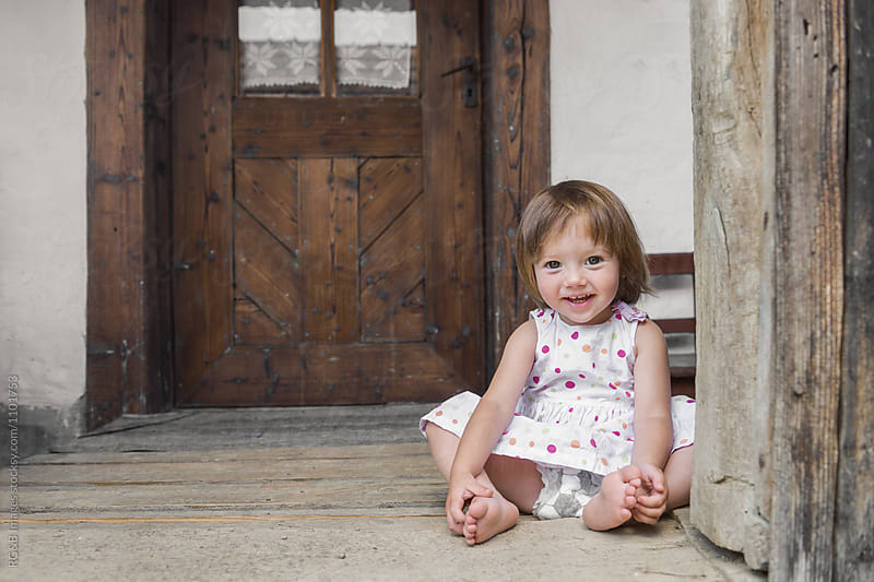 Single infant girl sitting on wood floor smiling by RG&B Images for Stocksy United