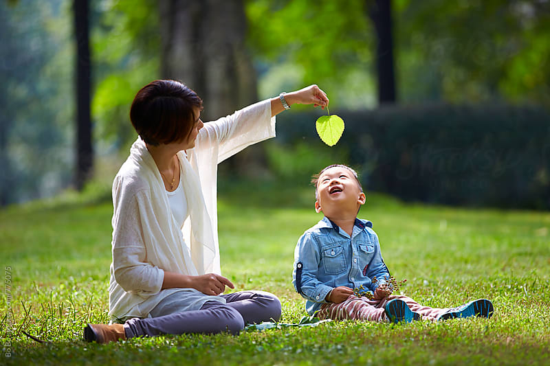 happy little boy with his mother in the sunny park by cuiyan Liu for Stocksy United