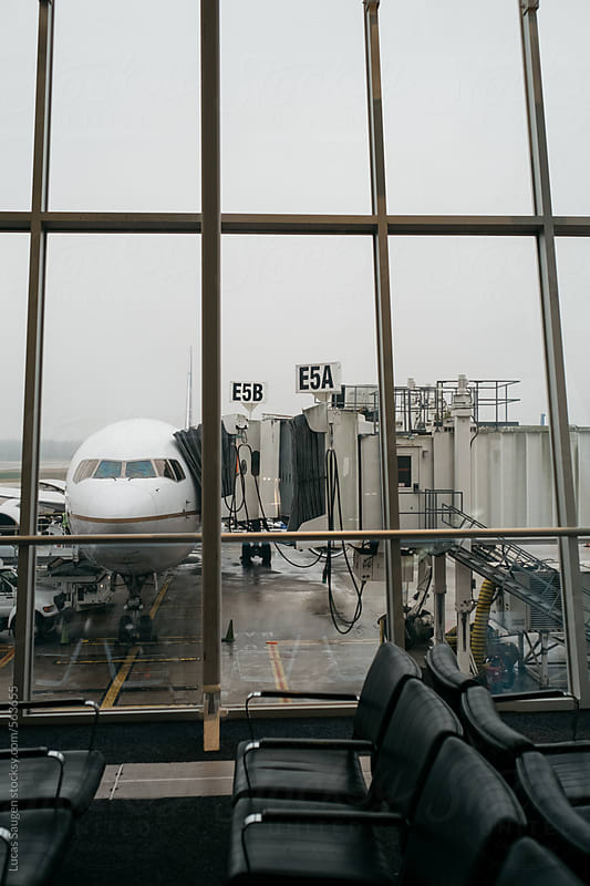Looking out an airport window at an airplane sitting at a jetway. by Lucas Saugen for Stocksy United