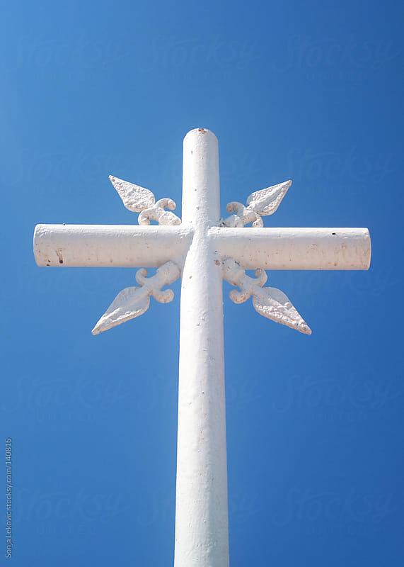 white cross against a blue sky by Sonja Lekovic for Stocksy United