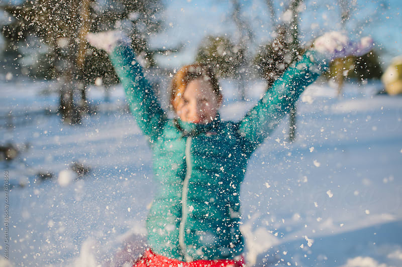 A young teenage girl plays in the snow. by Kelsey Gerhard for Stocksy United