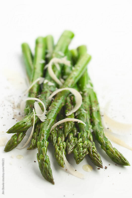 Asparagus with shaved cheese by JIm Bowie for Stocksy United