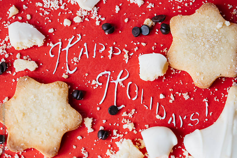 Happy holidays written with whipped cream, with star biscuits anch chocolate by Beatrix Boros for Stocksy United