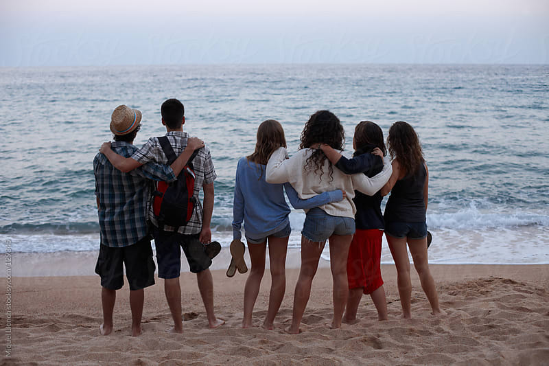 Group of teenagers in a mediterranean beach contemplating the sea after sunset by Miquel Llonch for Stocksy United
