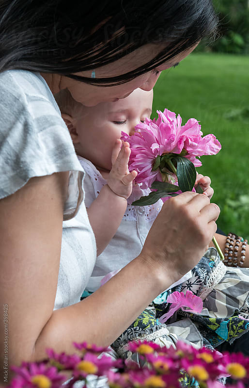 Baby smelling flower in mother's lap by Mick Follari for Stocksy United