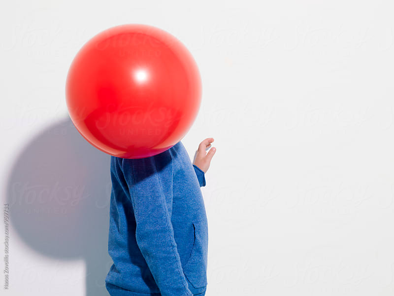 A balloon in front of a kid's face by Nasos Zovoilis for Stocksy United