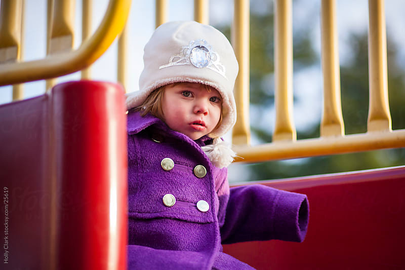 Young Girl Sitting on Playground Equipment by Holly Clark for Stocksy United