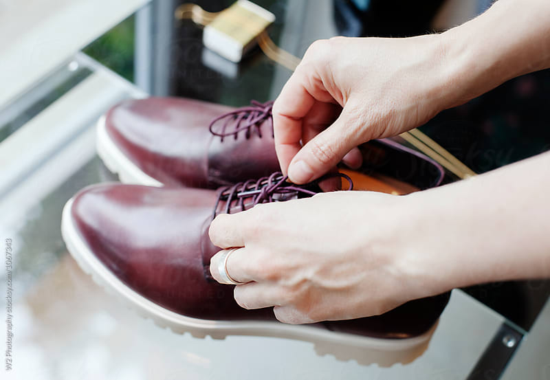 Store employee arranging shoes in a window display. by W2 Photography for Stocksy United