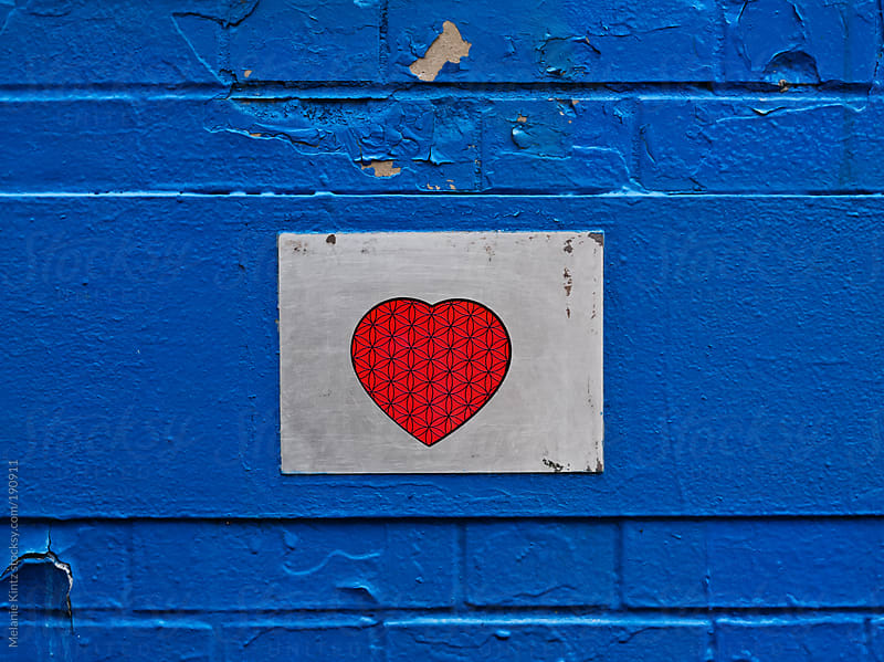 Blue wall and red heart by Melanie Kintz for Stocksy United