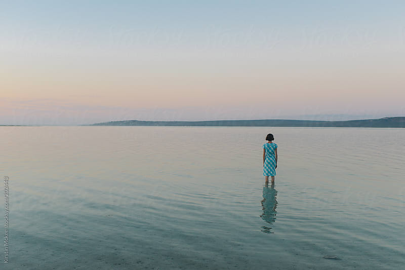 Lone girl standing in a lagoon at sunset by Kirstin Mckee for Stocksy United