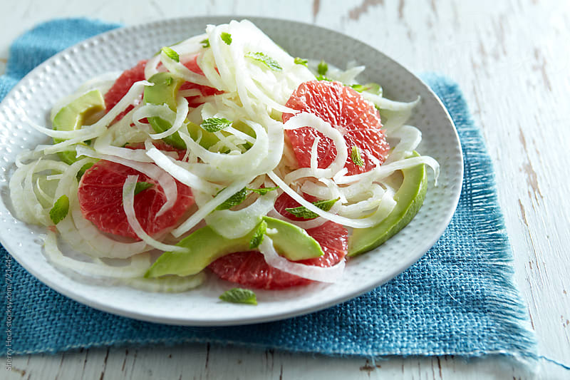 Salad of fennel, pick grapefruit, avocado without dressing on a white plate by Sherry Heck for Stocksy United