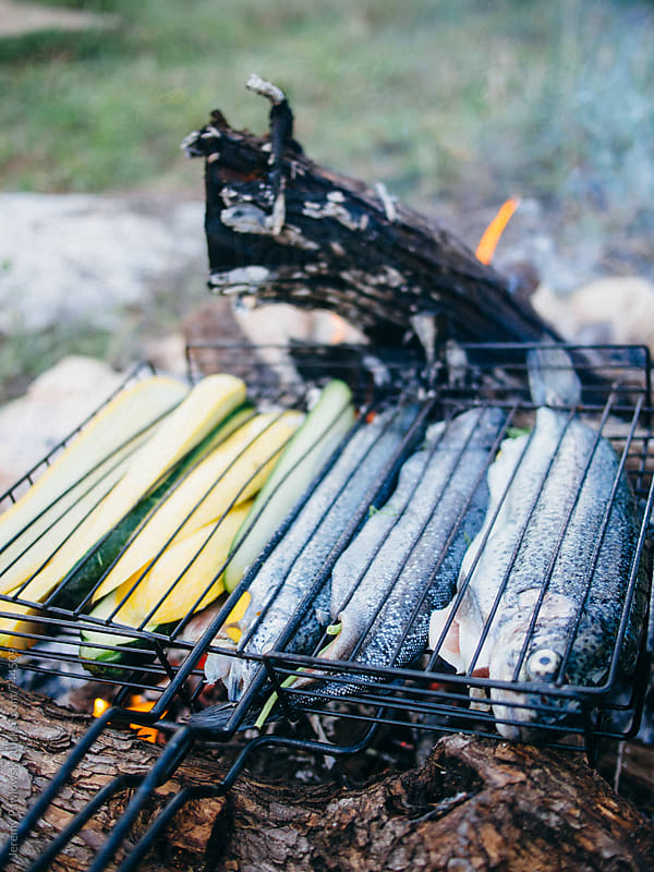 Fish and vegetables cooking on fire by Jeremy Pawlowski for Stocksy United