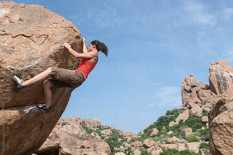 Young woman rock climbing to the top of a boulder  by RG&B Images for Stocksy United