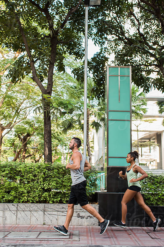 Two People Jogging in the City by Mosuno for Stocksy United
